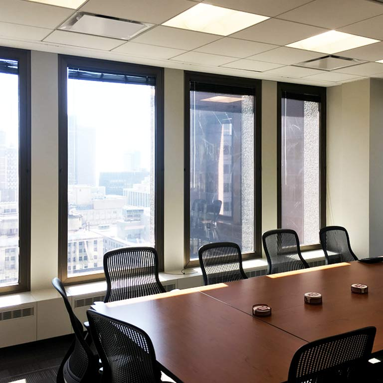 A wooden conference table with black chairs around it and a city view outside the windows.