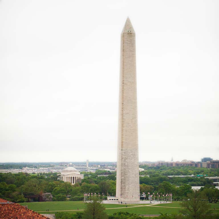 A view of a tall white pillar—the Washington Monument—in the middle of a green lawn